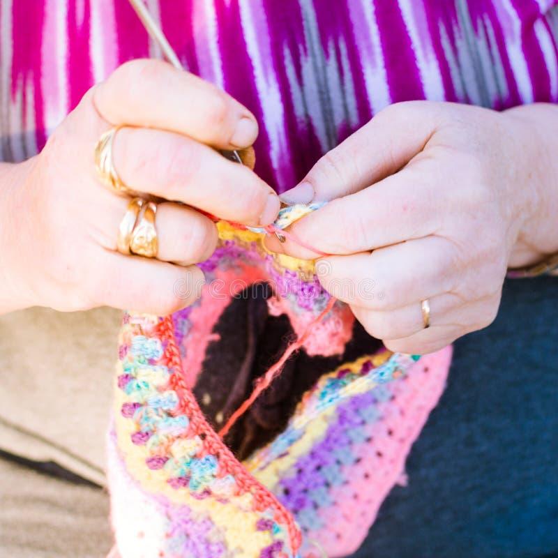 Senhora idosa que faz malha em agulhas de confecção de malhas, usando lãs coloridas Passatempo para pessoas adultas imagens de stock