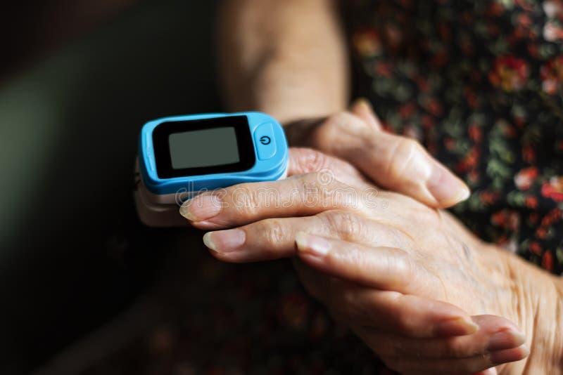 Senhora idosa que mede sua saturação do oxigênio com um oxímetro do pulso imagens de stock royalty free
