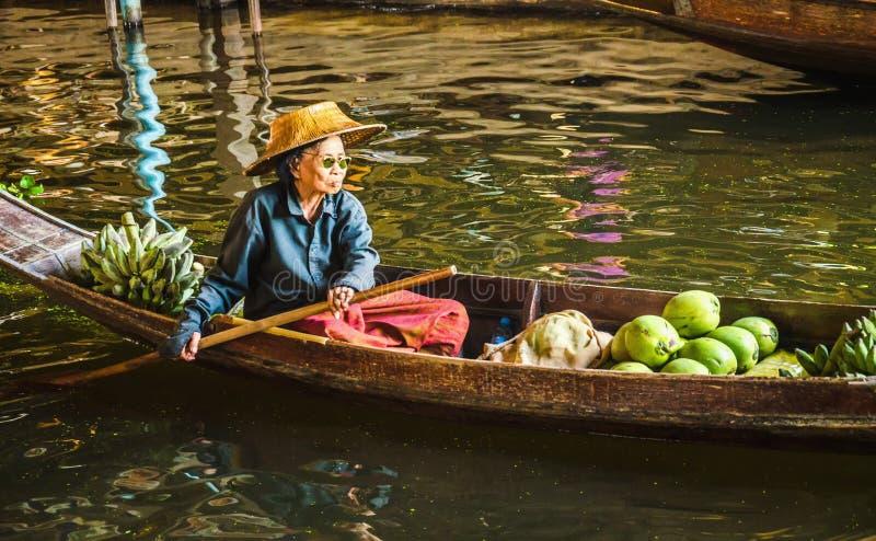 Senhora idosa que vende o alimento no mercado de flutuação, Tailândia foto de stock