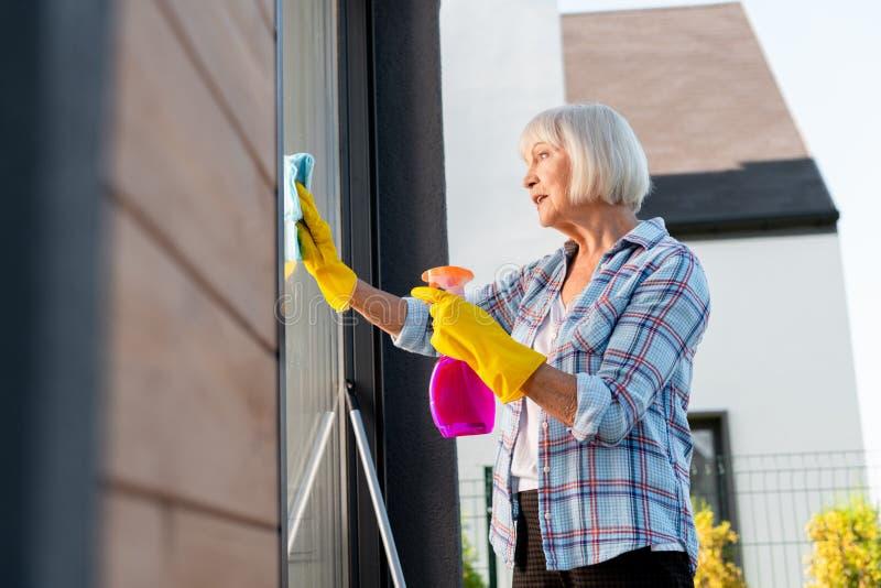 Senhora idosa que veste as luvas amarelas brilhantes que sentem janelas de lavagem ocupadas fotografia de stock royalty free
