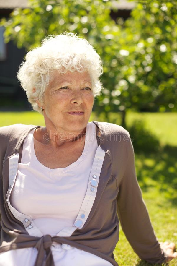 Senhora idosa relaxado que senta-se fora fotografia de stock royalty free