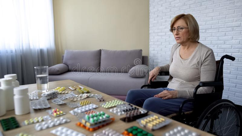 Senhora idosa só que senta-se na cadeira de rodas perto da tabela com a medicina que sente comprimida fotos de stock