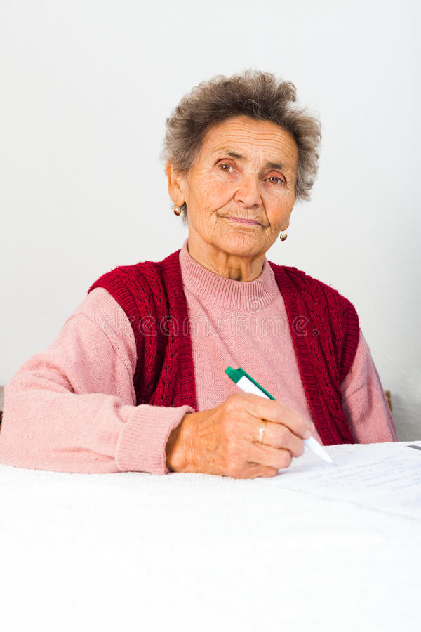 Senhora idosa Signing Contract imagens de stock royalty free