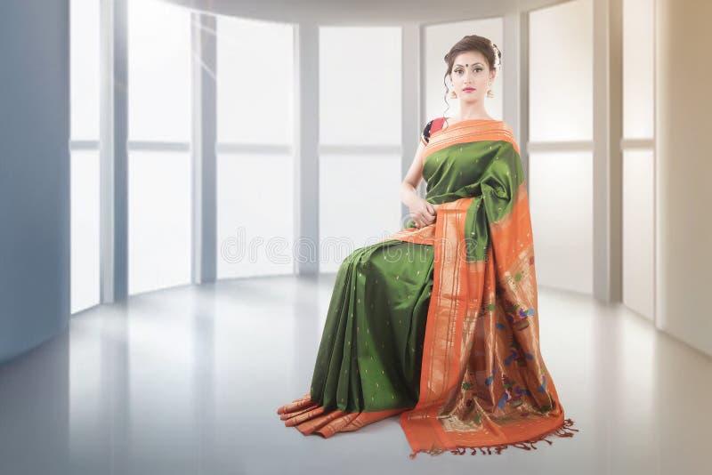 Senhora indiana no saree verde que senta-se na cadeira fotos de stock