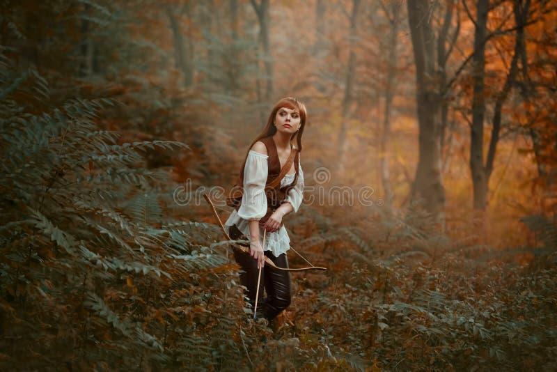 A senhora lindo com cabelo vermelho longo na roupa de couro segue o animal selvagem, caça para baixo a rapina na floresta úmida,  imagens de stock