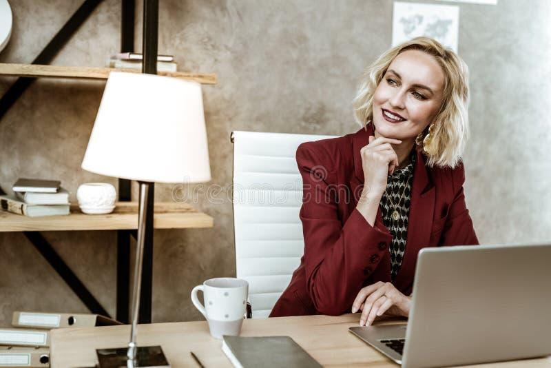 Senhora loura bonita de irradiação no traje escuro que olha para fora a janela fotografia de stock royalty free