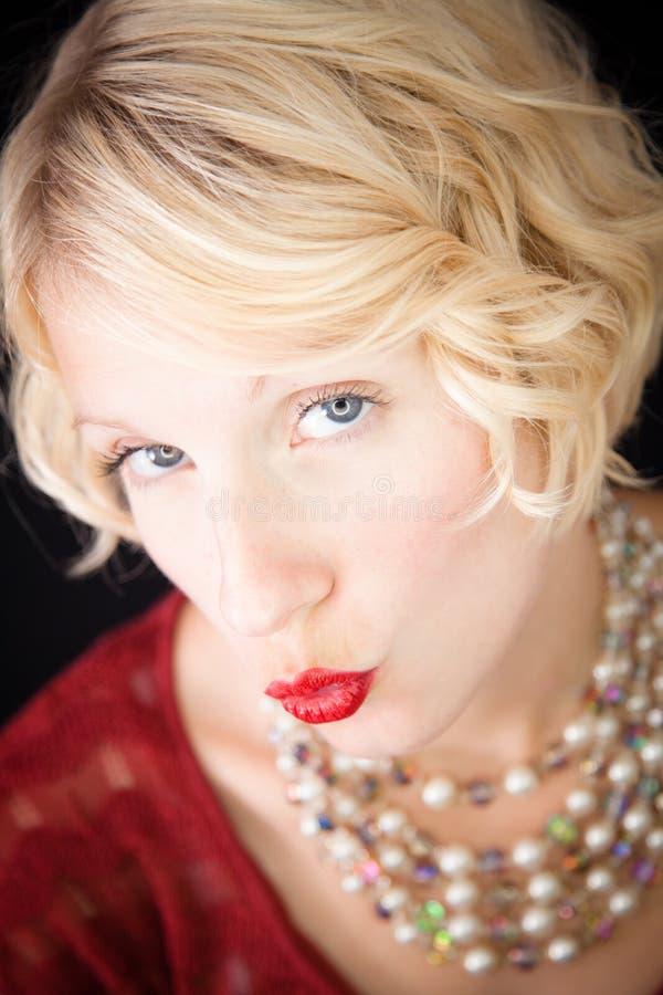 Senhora loura bonita que envia beijos na câmera foto de stock royalty free