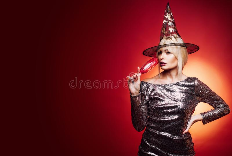 Senhora loura de Gelightful com um vidro do champanhe no fundo vermelho Mulher surpreendida bonita nas bruxas chapéu e traje imagens de stock royalty free