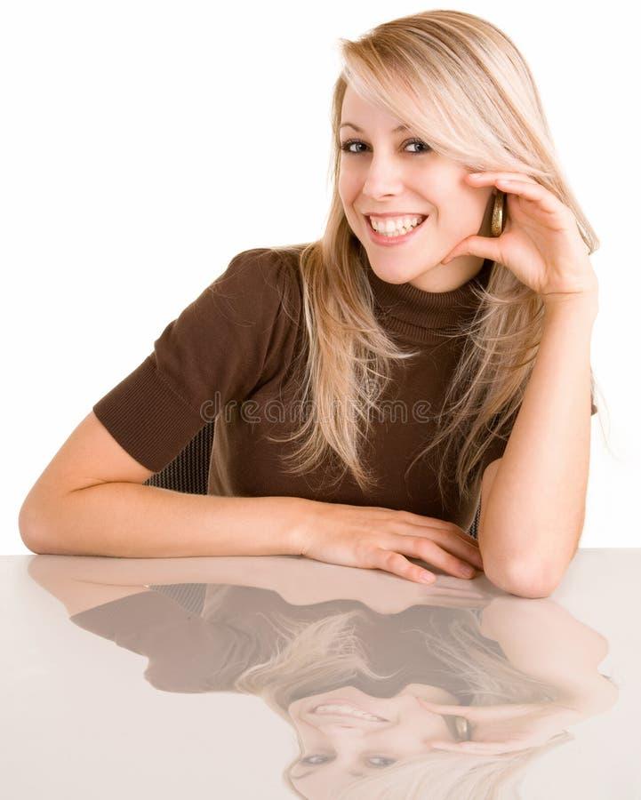 Senhora loura de sorriso Sitting em sua mesa imagem de stock royalty free
