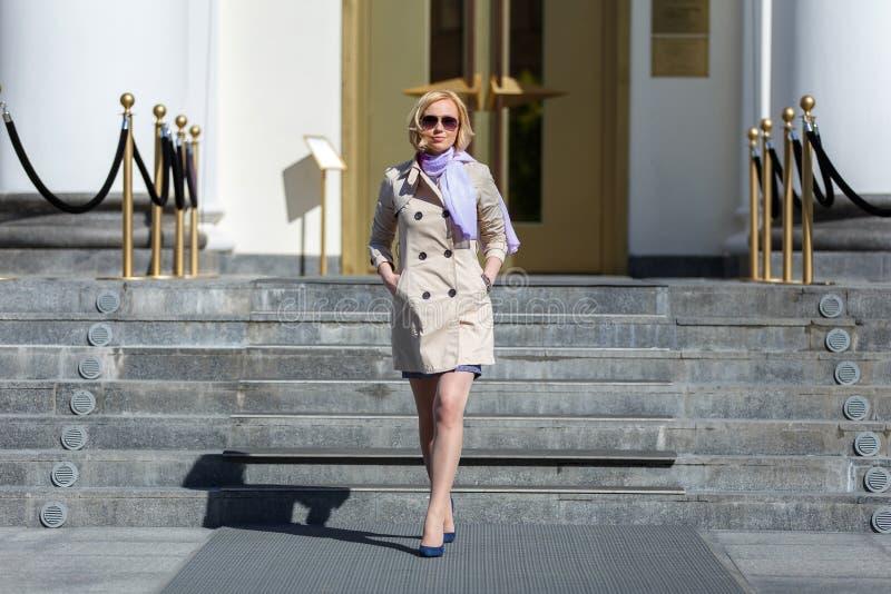 Senhora loura elegante do negócio no passeio dos vidros de sol foto de stock royalty free