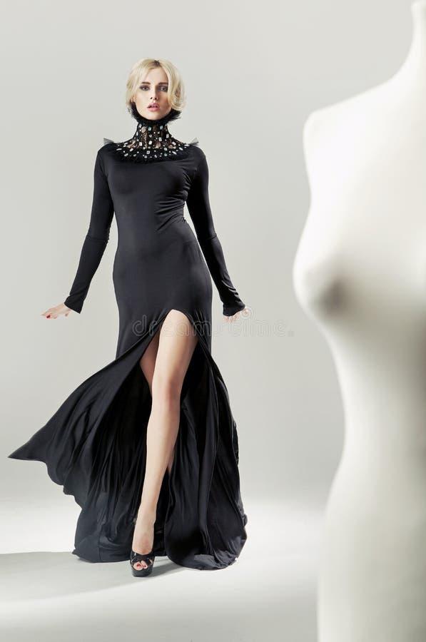 Senhora loura escultural, fascinando no vestido preto imagens de stock royalty free