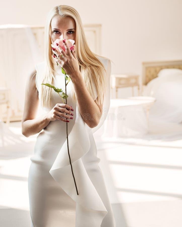 Senhora loura esperta que cheira uma rosa foto de stock royalty free