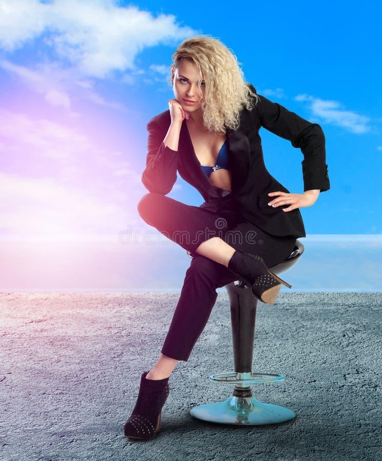 A senhora loura nova do negócio com olhos azuis senta-se na cadeira fotografia de stock royalty free