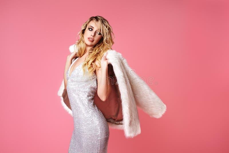 Senhora loura nova no vestido da forma, casaco de pele Mulher 'sexy' que levanta no fundo cor-de-rosa na roupa elegante luxuosa,  foto de stock