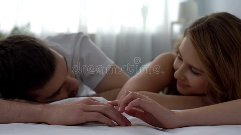 Senhora loving bonita que toca na mão do marido maciamente do sono, lua de mel imagem de stock