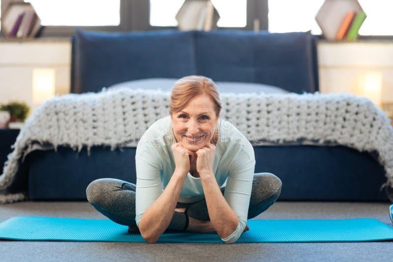 Senhora madura flexível que está no grande humor ao sentar-se na postura dos lótus imagens de stock royalty free
