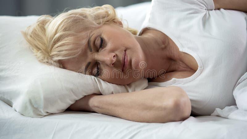 Senhora madura loura bonita que encontra-se no close-up da cama, sono saudável, aposentadoria imagens de stock