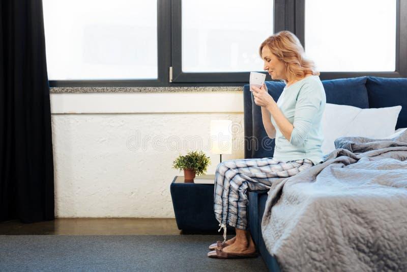 Senhora madura luz-de cabelo agradável que senta-se na borda de sua cama imagens de stock