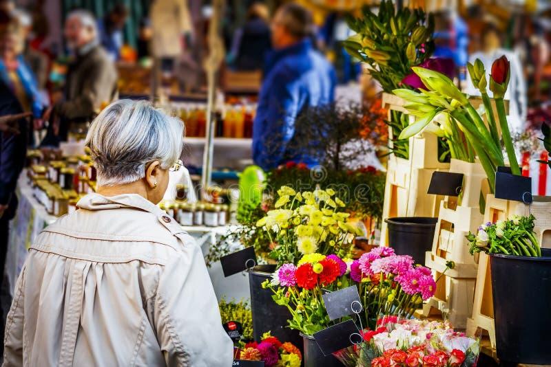 Senhora madura que olha flores no mercado semanal imagem de stock royalty free