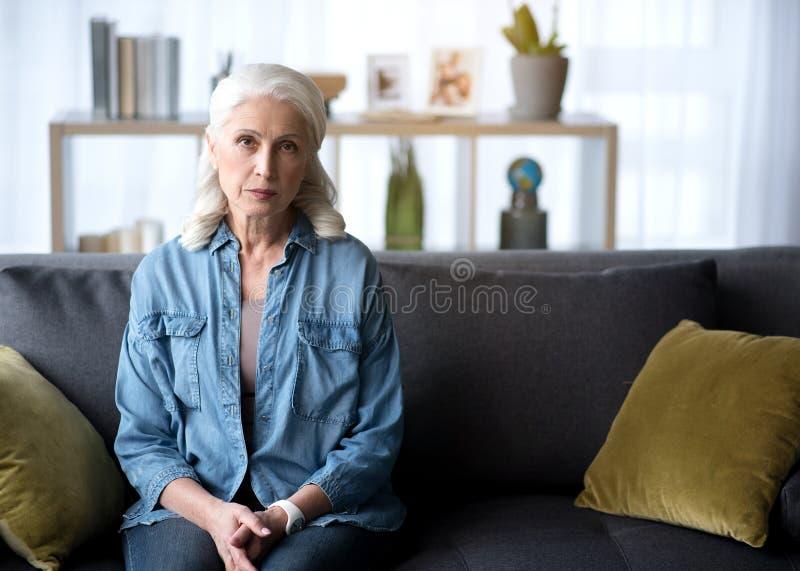 Senhora madura séria que localiza no sofá em casa foto de stock