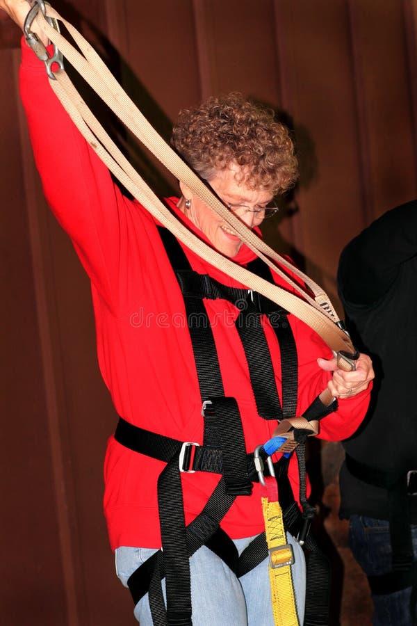 Senhora mais idosa Inspecting Zipline Gear foto de stock royalty free