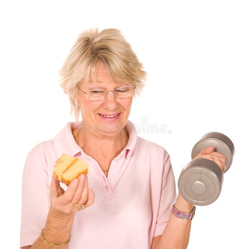 Senhora mais idosa madura que escolhe a dieta ou o exercício imagens de stock