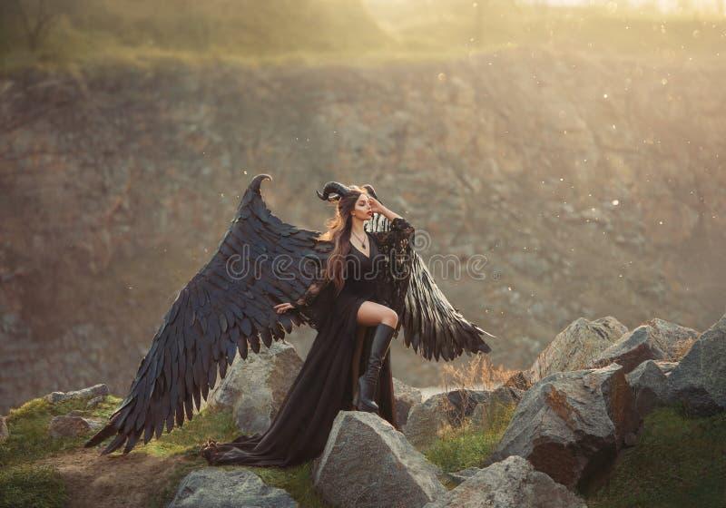 Senhora misteriosa no vestido leve preto do laço com trem longo, menina com pé aberto nas botas de couro, anjo horned escuro de foto de stock