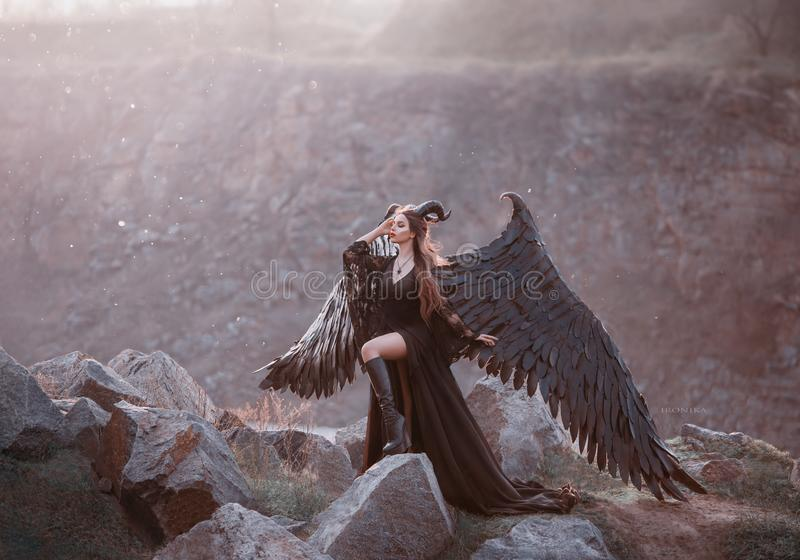 Senhora misteriosa no vestido leve preto do la?o com trem longo, menina com p? aberto nas botas de couro, anjo horned escuro de fotos de stock royalty free