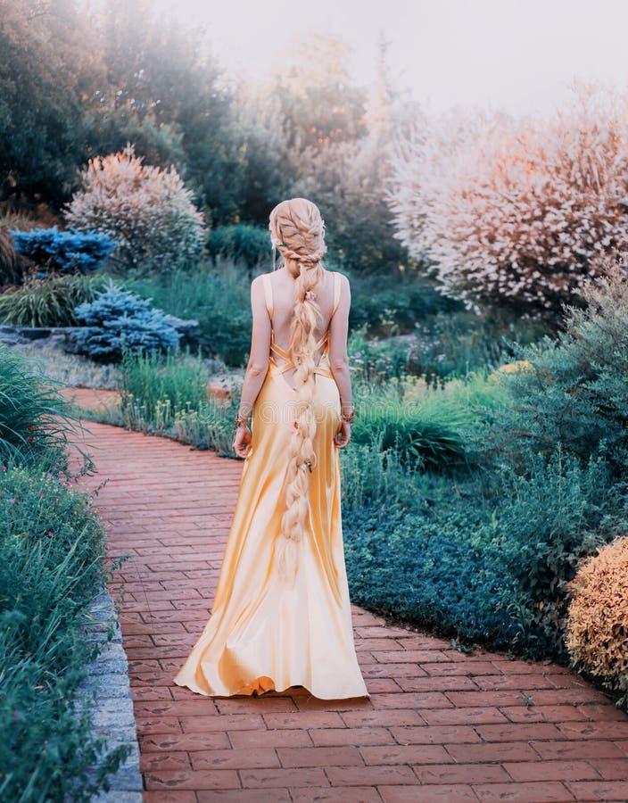 Senhora misteriosa no vestido luxuoso caro amarelo chique no jardim magnífico, princesa misteriosa com cabelo louro longo imagem de stock