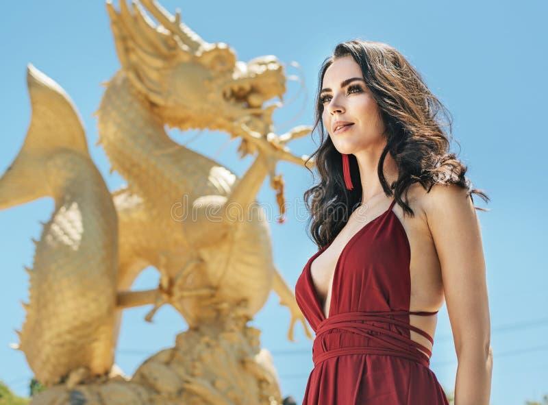 Senhora moreno bonita que levanta com um dragão dourado no fundo foto de stock