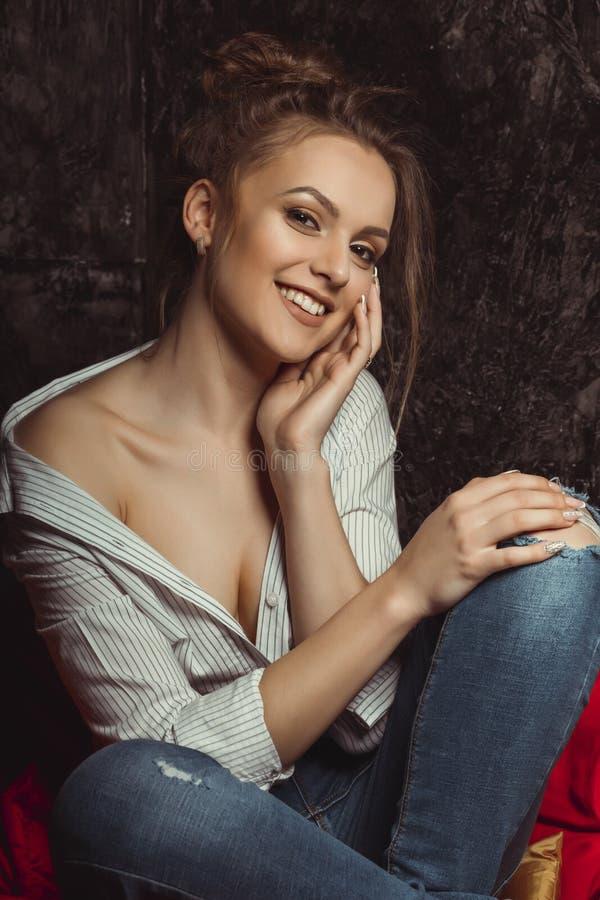 Senhora moreno de sorriso com composição natural na camisa e no jea rasgado imagem de stock