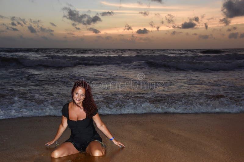 Senhora moreno madura bonita que ajoelha-se na areia na frente do por do sol foto de stock royalty free