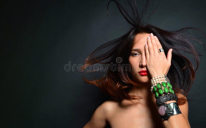 Senhora moreno nova com os acessórios luxuosos isolados no fundo preto foto de stock