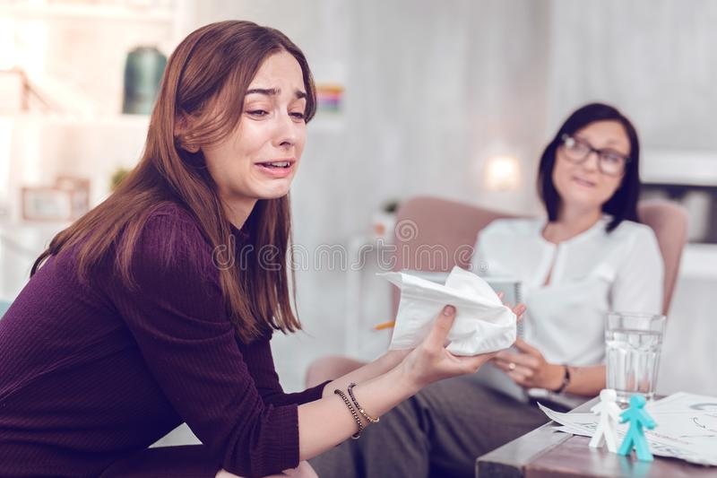 Senhora moreno nova de grito da virada que vai emocional durante a terapia fisiol?gico fotografia de stock royalty free