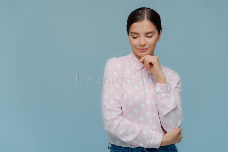A senhora moreno pensativa guarda o queixo, focalizado para baixo, pensa sobre algo, veste a blusa elegante do às bolinhas e as c imagens de stock