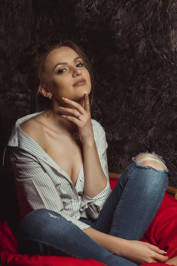 Senhora moreno sensual com composição natural na camisa e no jea rasgado fotos de stock