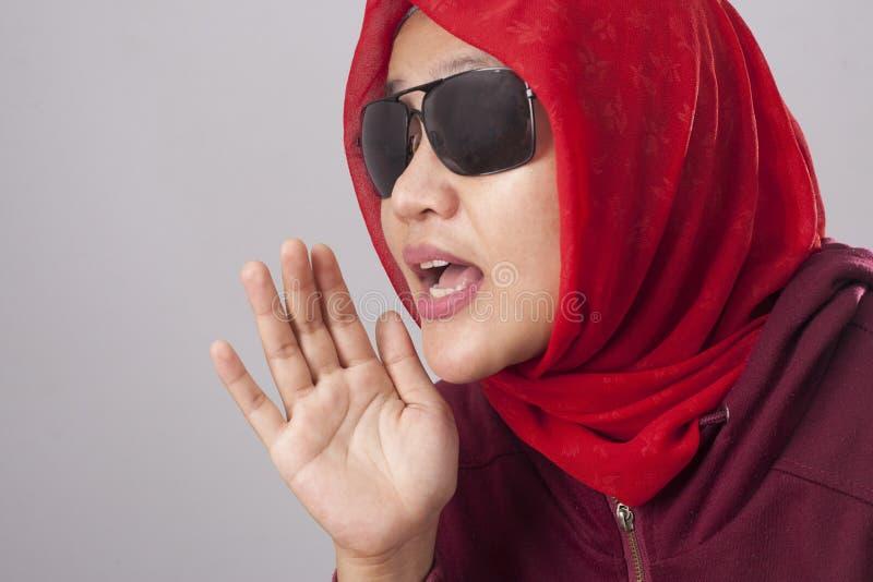 Senhora muçulmana em vermelho sussurrando algo fotografia de stock royalty free