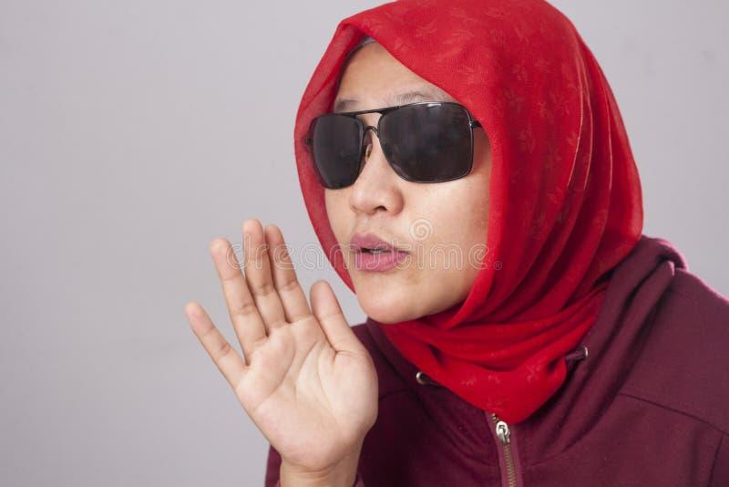 Senhora muçulmana em vermelho sussurrando algo fotos de stock