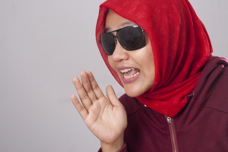 Senhora muçulmana em vermelho sussurrando algo imagem de stock