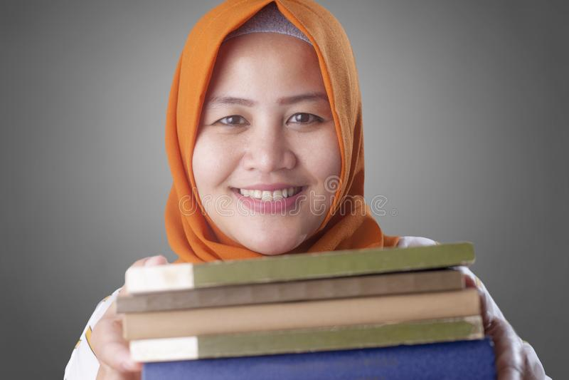 Senhora muçulmana feliz com livro fotos de stock