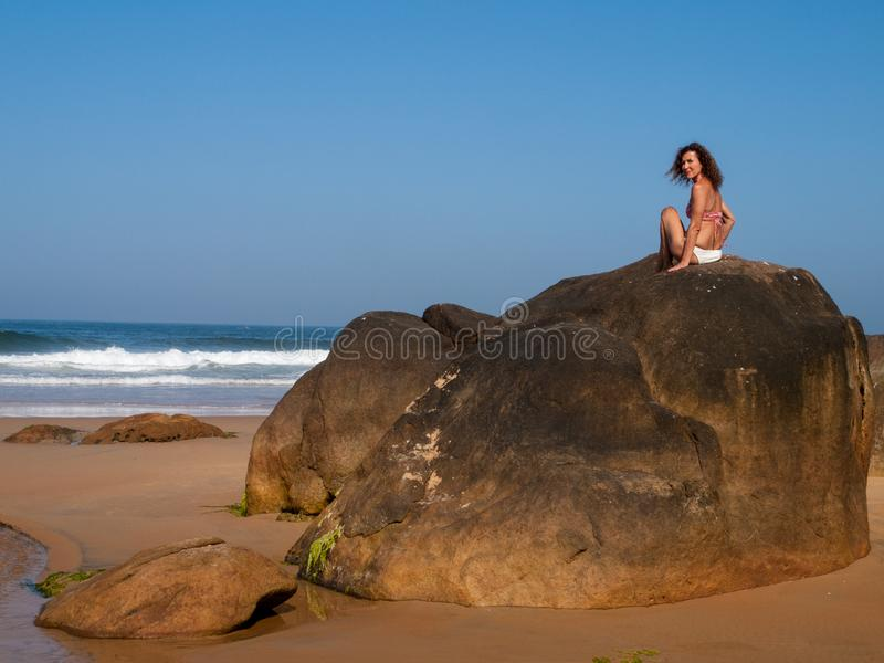 Senhora na rocha do mar fotografia de stock