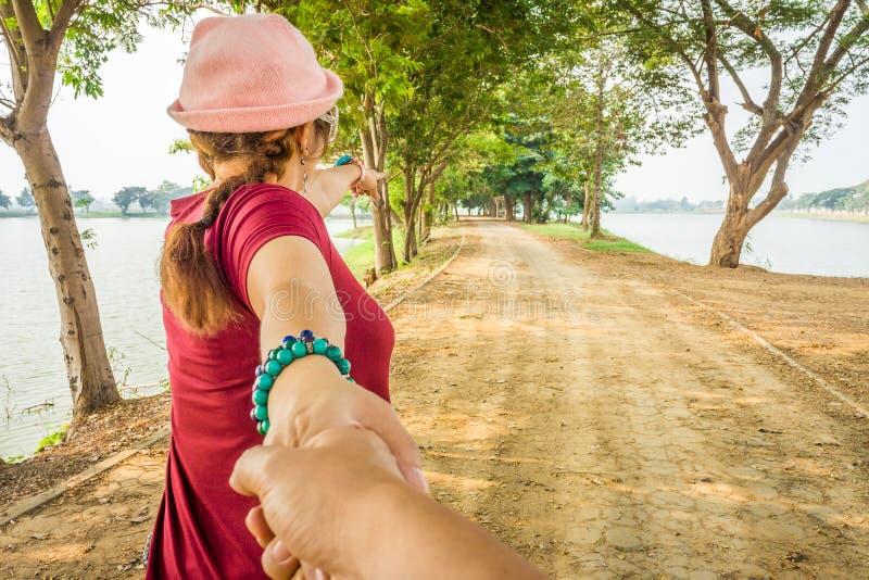 A senhora no pano vermelho que aponta seu dedo e conduz seu amante pela mão na estrada pavimentada fotos de stock royalty free