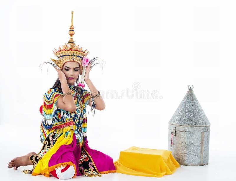 A senhora no terno de dança clássica tailandês do sul está levantando no fundo branco está pondo a mantilha sobre sua cabeça, fotos de stock