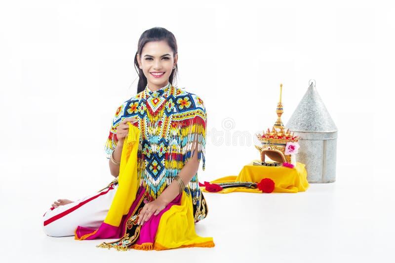 A senhora no terno de dança clássica tailandês do sul está sentando-se no fundo branco fotografia de stock