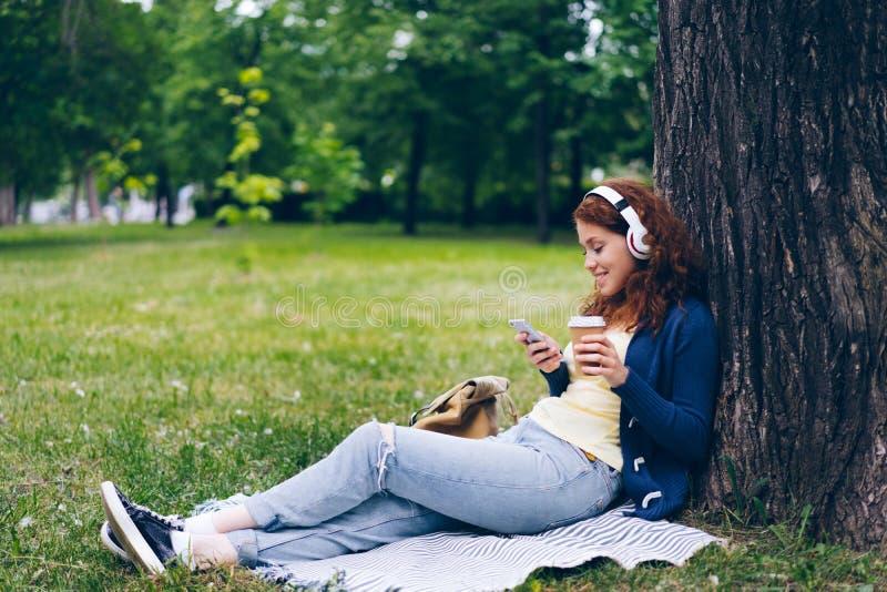Senhora nos fones de ouvido que aprecia a música usando o café bebendo do smartphone no parque fotos de stock royalty free