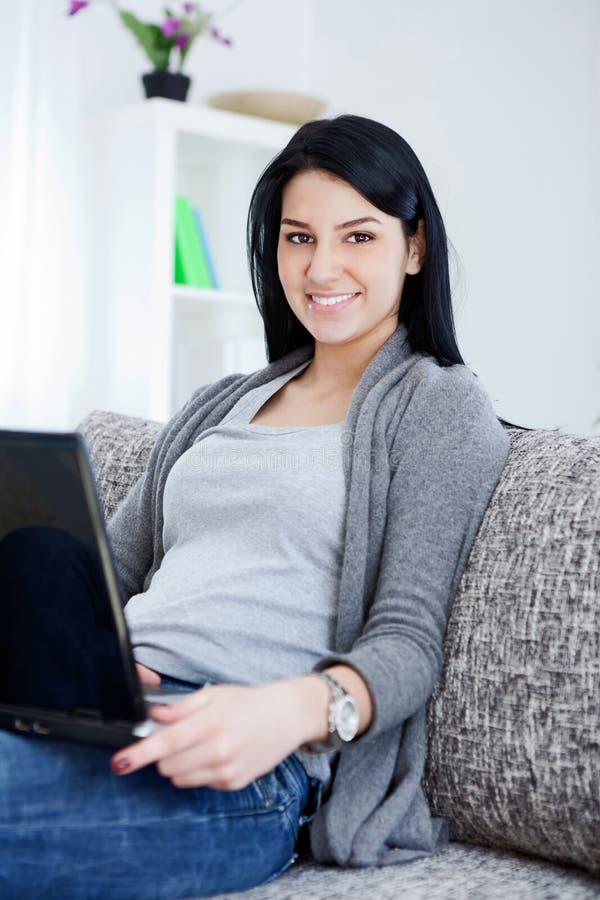 Senhora nova de sorriso que senta-se no sofá, usando o portátil fotografia de stock royalty free