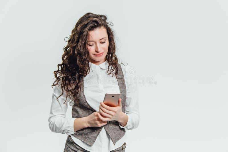 A senhora nova do negócio com cabelo encaracolado bonito em um fundo branco exulta Durante isto, sorri ao guardar fotos de stock royalty free