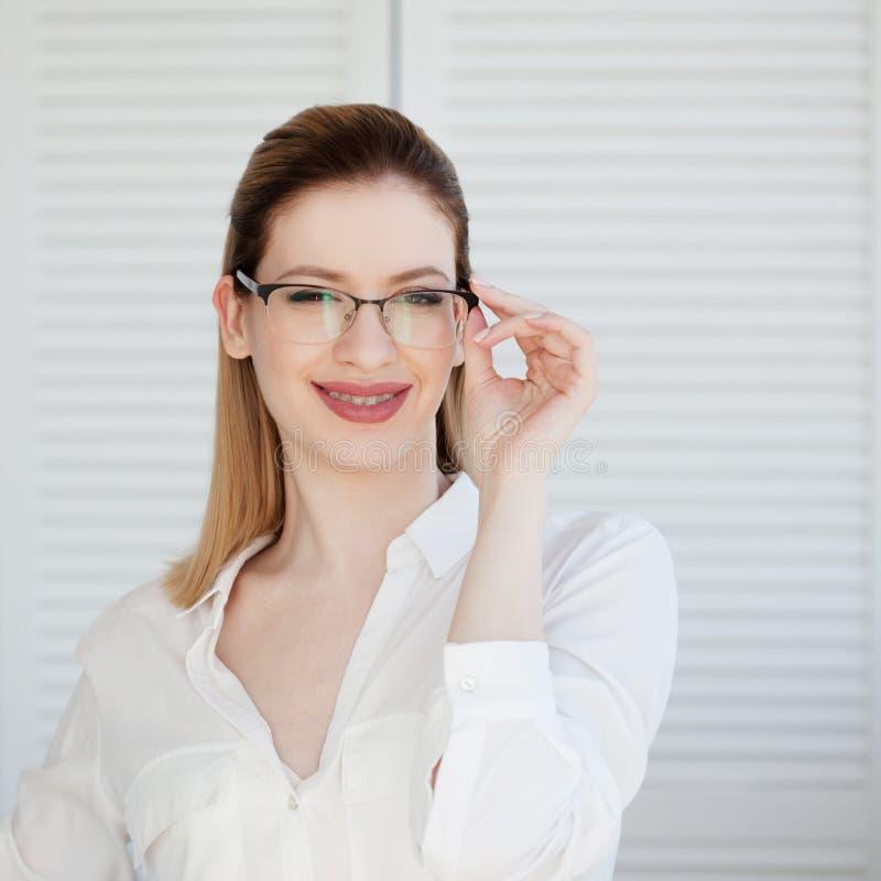 Senhora nova do negócio na camisa e nos vidros brancos Sorriso atrativo da mulher nova foto de stock royalty free