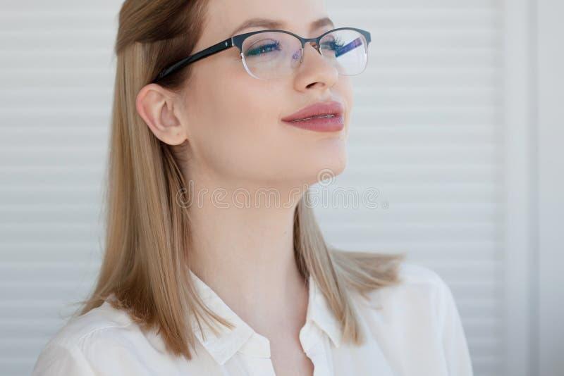 Senhora nova do neg?cio na camisa e nos vidros brancos Sorriso atrativo da mulher nova imagens de stock