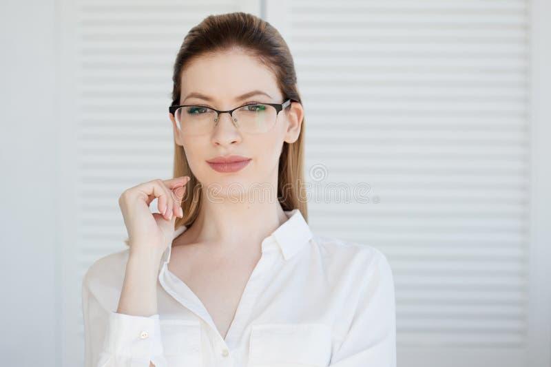 Senhora nova do neg?cio na camisa e nos vidros brancos Sorriso atrativo da mulher nova fotografia de stock royalty free